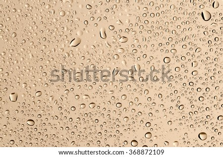 Water drops on glass, and a beige background. - stock photo