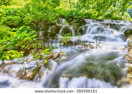 waterfalls on slopes of mountains and bridge