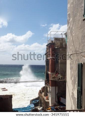 waves breaking on protective wall Riomaggiore Cinque Terre Italy Italian Riviera    - stock photo