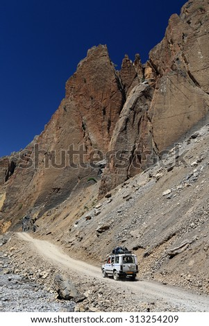 4WD Car on dirt road beside high rock mountain, Northern India. - stock photo