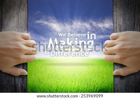 """""""We believe in making a difference"""" Motivational quotes. Hands opening a wooden door then found a texts floating among new world as green grass field, Blue sky and the Sunrise. - stock photo"""