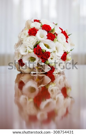 Wedding bouquet of roses and lilies on the table against the background of a bright window. - stock photo