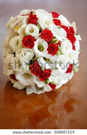 Wedding bouquet of roses and lilies on the table against the background of a bright window.
