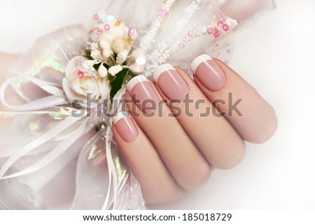 Wedding manicure on female hand with festive decoration of white ribbons and flowers. - stock photo