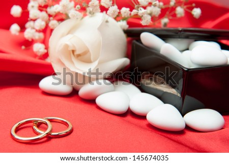 wedding rings and wedding favors on  elegant fabric background