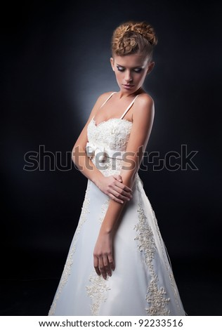 Wedding style - pretty supermodel fashionable young woman posing in white bridal dress in studio