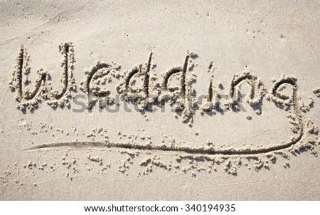 """""""Wedding"""" written on sand beach - stock photo"""