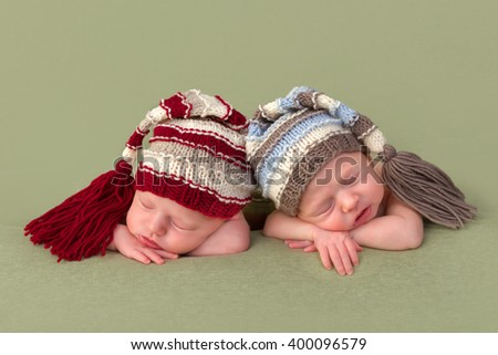 3 weeks old identical twin girls sleeping on a green backdrop - stock photo