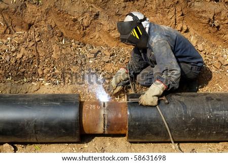 Welder working   pipeline - stock photo