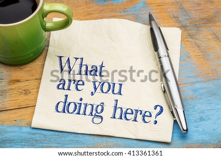 -What are you doing here? Handwriting on a napkin with cup of coffee against gray slate stone background