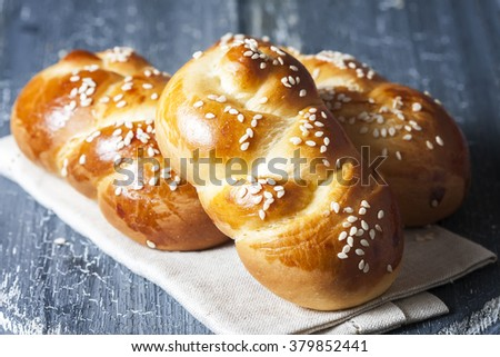 wheat buns with sesame seeds on a dark wooden background. selective focus - stock photo