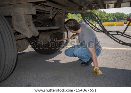 18-Wheeler Pre-trip Tire Inspection - A professional driver is using a tire thumper to check the tires underneath his trailer prior to driving OTR.   - stock photo