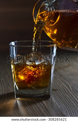 whiskey with ice in bar on old wooden table