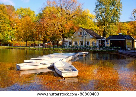 white boats on the lake in the autumn park - stock photo