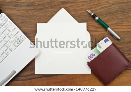 White envelope with a pen, money and a computer  - stock photo