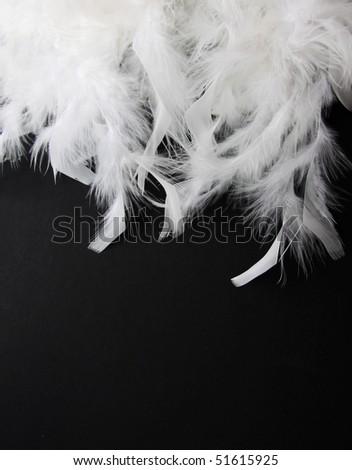 White feather on black background - stock photo