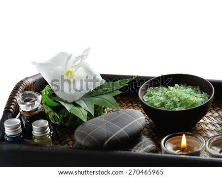 white flower with candle and massage stones on platter, isolated on white  - stock photo
