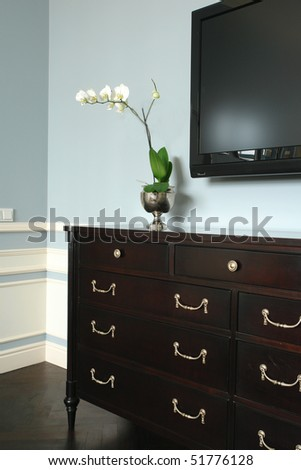 white flowers on the chest of drawers - stock photo