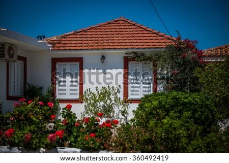 White greek house with garden - stock photo
