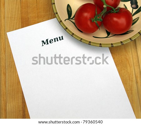 White paper with word  MENU and copy space on cutting board with decorative Italian bowl of red tomatoes on the vine.