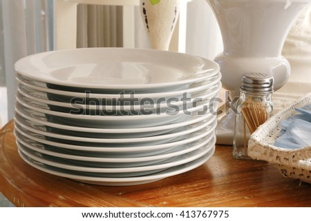 white plate stack on wood table, clean white plate and spoon in tray near fabric blind and window in luxury resort and hotel