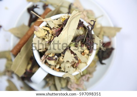White tea cup filled with  winter tea with cinnamon sticks on white background. Herbal tea on white background with copy space.