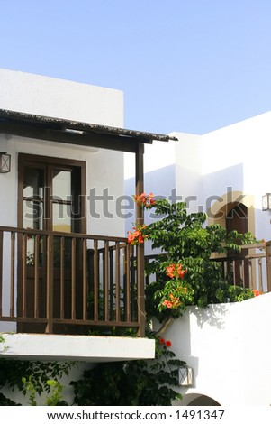White wash stone house with balcony, flowers growing by the wall. - stock photo