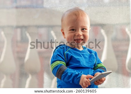 """""""who is speaking?"""". Cute baby with mobile phone - stock photo"""