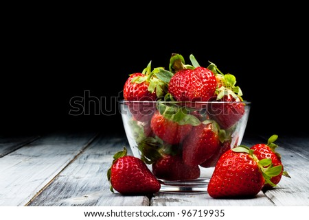 whole strawberry on bowl in a wood table - stock photo