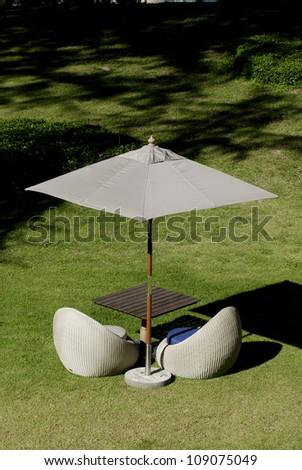 Wicker furniture and umbrella in green park. - stock photo