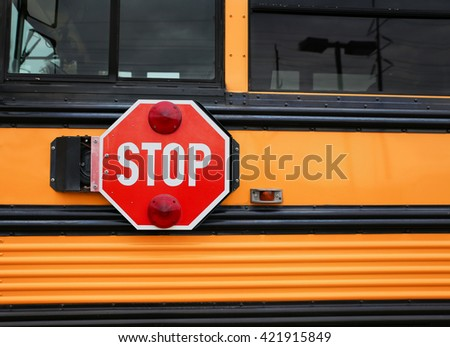 wide angle front view of a bright yellow orange school bus and the big red stop sign  - stock photo