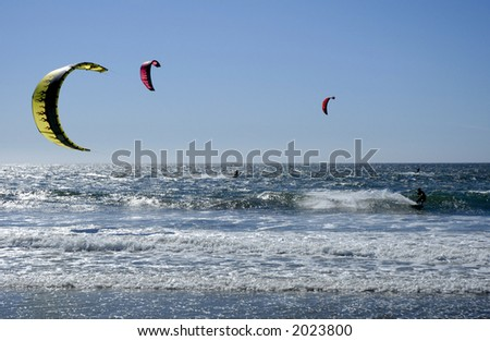 3 windsurfers, their surfboards and parasails in the Pacific Ocean