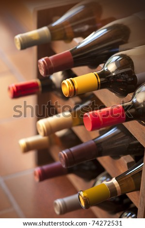 Wine bottles in vertical shot stacked on wooden racks shot with limited depth of field - stock photo
