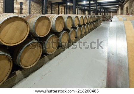 winery with  wooden barrels in rows - stock photo