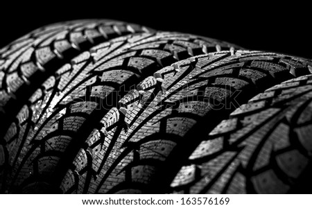 winter car tyre on a black background - stock photo