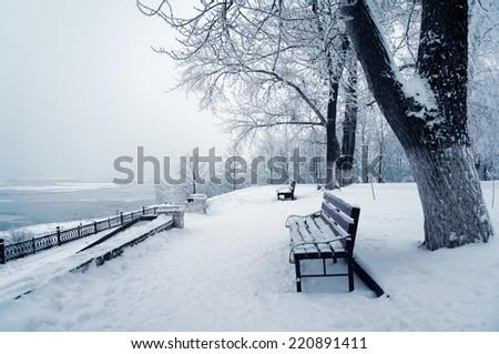 Winter nature, bench in snow on coast of river Volga - stock photo