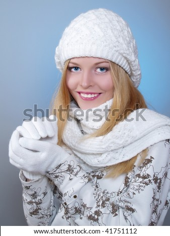 winter portrait of a pretty girl is freezing with a cap and a scarf and snowflakes