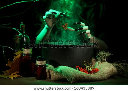 Witch in scary Halloween laboratory on dark color background - stock photo