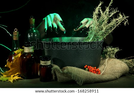 Witch in scary Halloween laboratory on dark color background