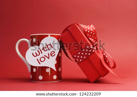 """With love"" message on red polka dot mug and red gift with polka dot ribbon bow against a red background for a bright, fun and cheerful Valentines Day, Christmas, birthday or Mothers Day gift. - stock photo"