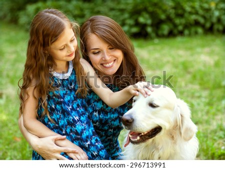 woman and her daughter with a dog playing in the park
