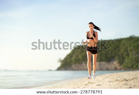 Woman at the beach running by the ocean at sunset - stock photo