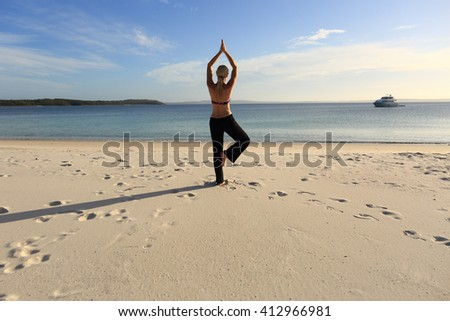 Woman balanced in a yoga pose standing barefoot on one leg with her hands joined above her head at the beach in late afternoon sunlight, drawing long shadows on the sand. Asana vrksasana. - stock photo