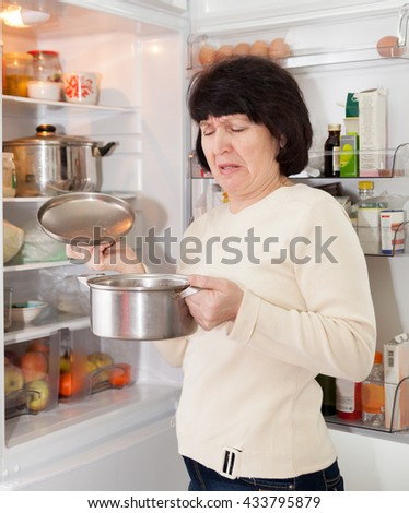 woman checking   food in   refrigerator at  kitchen.