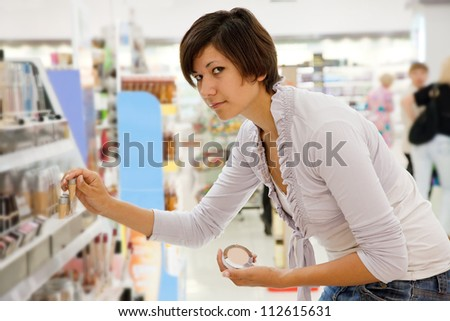 woman chooses cosmetic  at cosmetics  shop - stock photo
