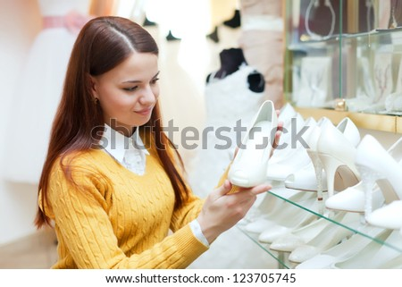 woman chooses white shoes at fashionable shop - stock photo