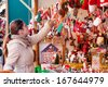 Woman choosing toys at Christmas market - stock photo