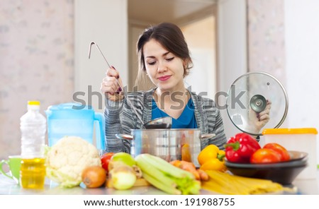 woman cooking veggie soup with laddle in  kitchen  at home  - stock photo
