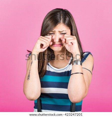 Woman crying and wiping tears against pink background - stock photo