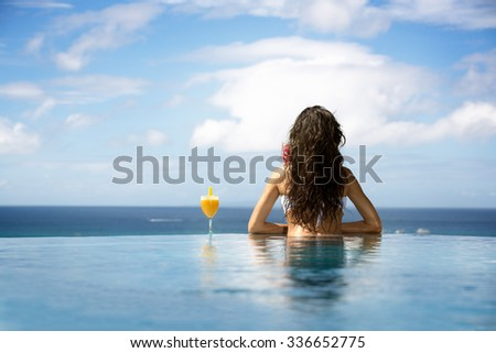 woman enjoying cocktail in a swimming pool, back view - stock photo